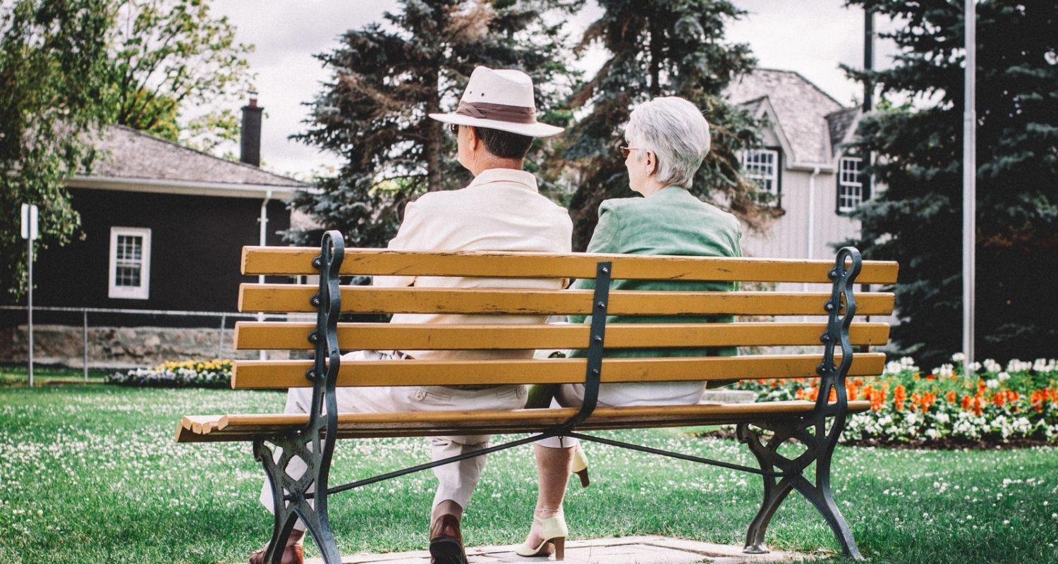 man and woman sitting on brown wooden bench during daytime